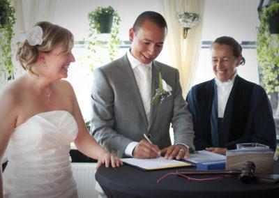 Bruidspaar en Babs Anke Minnee zetten glimlachend hun handtekening