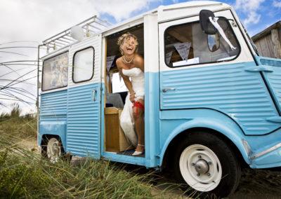 Vrolijke bruid in ludieke trouwauto
